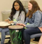 Two SAGE STEAM Campers playing the bongos